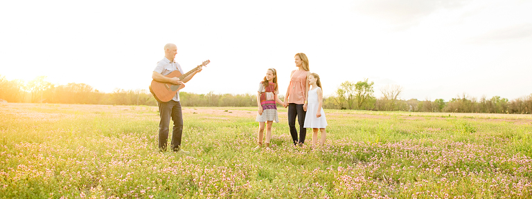 Husband plays guitar with wife and two children for a sunset photography session in overland park kansas