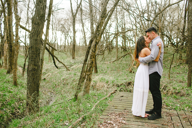 couple kissing in woods overland park engagement photography