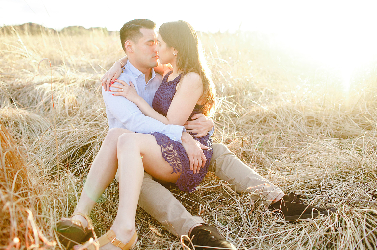 couple sits together in field overland park engagement photography