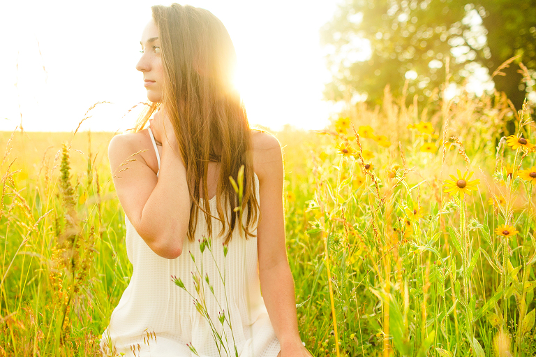 girl sits in field at sunset overland park senior photographer